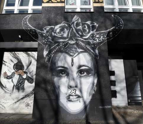 Streetart eines Frauenporträts mit Hörner und Rosenhut
