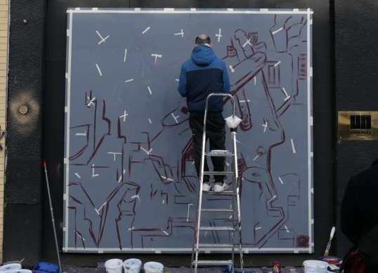 Mann malt Streetart