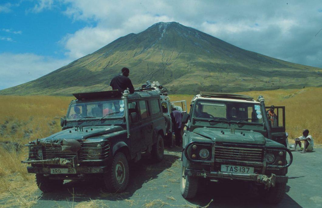 Jeeps vor einem mächtigen Vulkan in Afrika