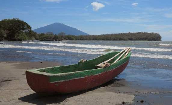 Boot an einem Strand, dahinter Vulkan