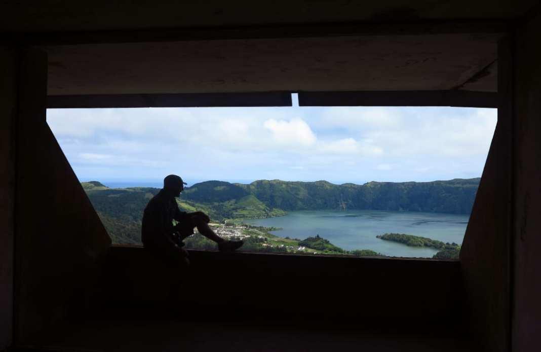Mann sitzt an Fenster mit Blick über See