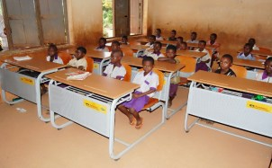 Pupils using new desk in their classroom