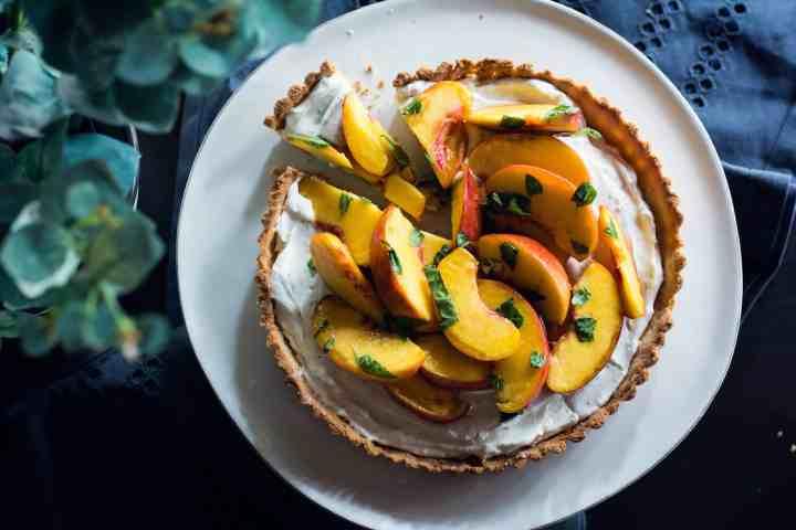 image of vegan peach basil tart with slice taken out of it