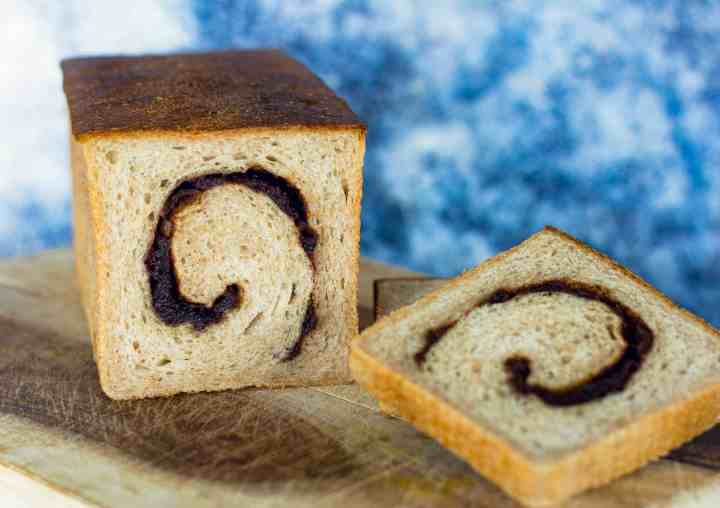image of cinnamon jujube swirl sourdough, with two slices on the side