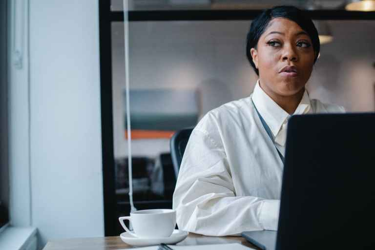 thoughtful black businesswoman working on project in office