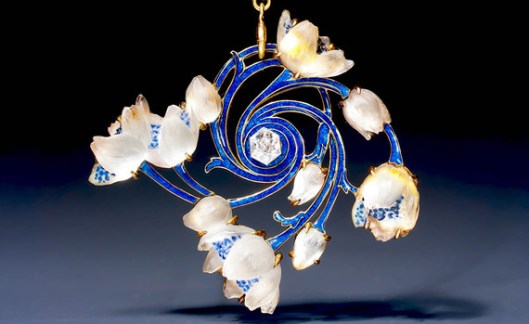 A magnificent Art Nouveau gold, diamond, enamel and glass 'wood-anemone' pendant by René Lalique, designed as glass wood-anemone flowers spiralling out from a hexagonal diamond, the branches applied with translucent blue enamel, on a rod and link blue enamel gold chain. Can also be worn as a brooch. Signed: Lalique. Paris, circa 1905. Provenance : Belgian private collection