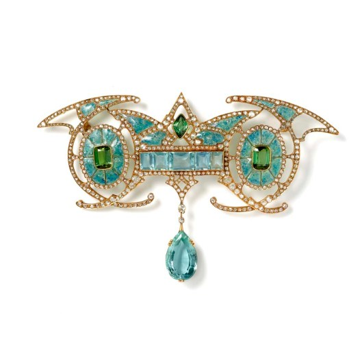 Art Nouveau yellow gold brooch designed with a central aquamarine panel carrying an aquamarine drop in between two green tourmalines within enamelled ovals with diamonds, by Georges Fouquet, Paris. Exhibited by Hancocks.
