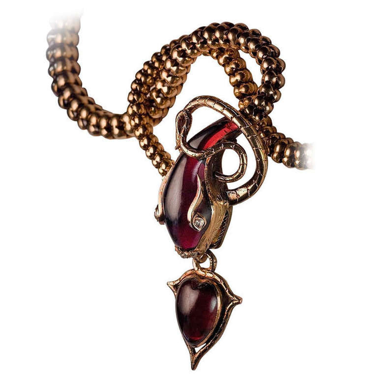 Snake Necklace. Superb Victorian era gold necklace is designed as a finely carved almandine garnet snake head holding an almandine garnet heart-shaped locket. The snake's eyes and nose are embellished with rose cut diamonds. The back of the heart-shaped pendant is set with a glazed miniature picture frame. On 1stdibs.