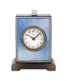 AN EARLY 20TH CENTURY ENAMEL AND DIAMOND MINUTE REPEATING DESK CLOCK, BY CARTIER (estimate £15,000 – £20,000). The circular cream dial with black painted Arabic numerals and rose-cut diamond-set hands, to the white enamel beaded bezel and blue guilloché enamel case, with further white enamel borders and central single rose-cut diamond star motif accents, with moonstone push piece, raised on a carved agate base, mechanical movement, circa 1915, 7.0cm high.