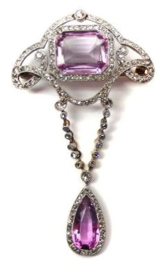 Belle Epoque Pink Topaz & Diamond Pendant Brooch, ca 1900, with a cut-corner rectangular pink topaz in an openwork diamond scroll frame of quatrelobe form, suspending a pear shaped topaz & diamond cluster from two articulated diamond lines, millegrain set in platinum & gold.