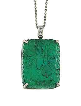 An emerald pendant The floral carved rounded rectangular emerald in claw mount to a circular-cut diamond three stone pendant loop and trace link neckchain, 4.3cm long. Estimate £5,000-6,000.