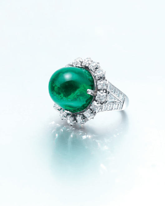 AN EMERALD AND DIAMOND RING, BY CARTIER Designed as a cabochon emerald, within a rectangular-shaped diamond surround, to the triangular and square-shaped diamond shoulders, mounted in platinum.