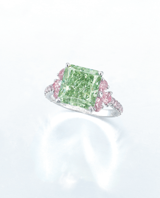 An exceptional coloured diamond ring by Moussaieff. Set with a rectangular-shaped fancy intense green diamond weighing approximately 5.02 carats, flanked by pear-shaped pink diamonds, to the brilliant-cut pink diamond gallery and three quarter-hoop, mounted in platinum.