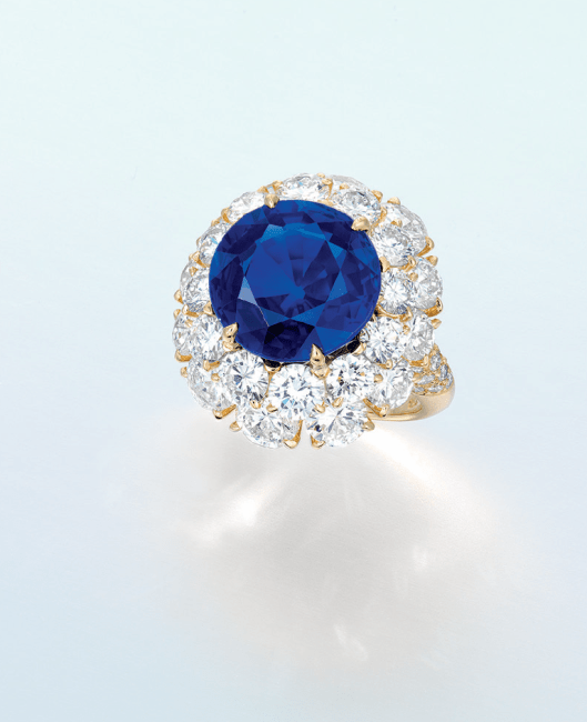 An exceptional sapphire and diamond ring. Set with a circular-cut sapphire weighing approximately 10.33 carats, within a brilliant-cut diamond two-tiered surround, extending to the quarter-hoop, mounted in 18k gold.