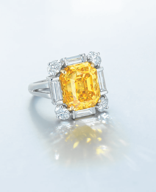 A RARE COLOURED DIAMOND AND DIAMOND RING Set with a rectangular-shaped fancy vivid orangy yellow diamond weighing approximately 9.50 carats, within a baguette and oval-shaped diamond surround, mounted in platinum and 18k yellow gold.