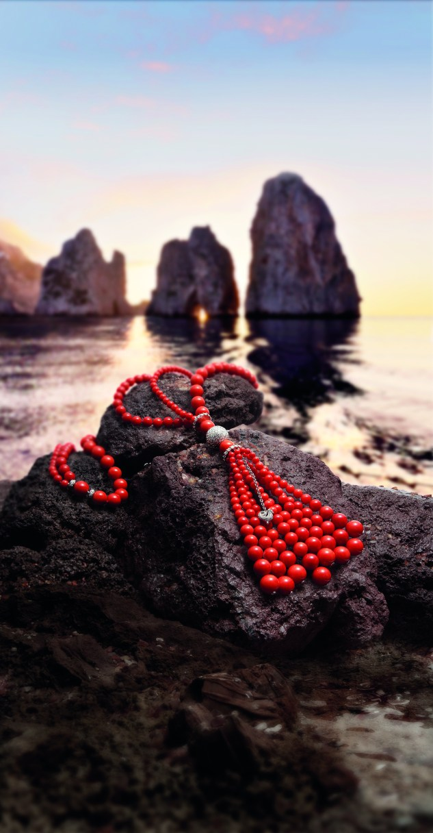 Sautoir Cherie, in red coral, and Capri's Faraglioni in the background.