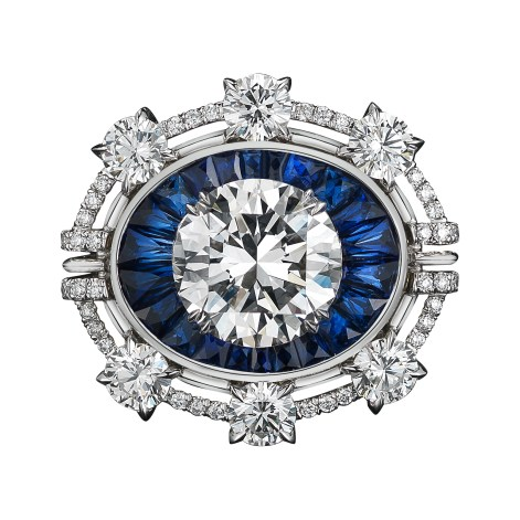 A one-of-a-kind Diamond ring comprised of 22 blue Sapphire Trapezoids totaling 2.80 carat weight and a 4.02 carat Brilliant-cut Diamond 'floating' in the center, surrounded by six 4mm round Diamonds, enhanced by Alexandra Mor sig- nature details of 1mm knife edged-wire and 1mm 'floating' Diamond melee. Platinum set on an 18-karat yellow gold AM logo gallery. Signed by artist. Crafted in the USA. Made-to-order.
