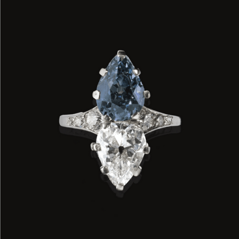 Set with a fancy deep greyish blue pear-shaped diamond weighing 2.89 carats and a colourlesspear-shaped diamond weighing 2.34 carats, the shank set with rose, single and circular-cut stones, mounted in platinum.