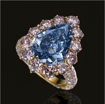 Set with a fancy vivid blue pear-shaped diamond weighing 4.16 carats, framed by brilliant-cut diamonds of pink tint, the hoop pavé-set with similar brilliant-cut stones, mounted in platinum and yellow gold.