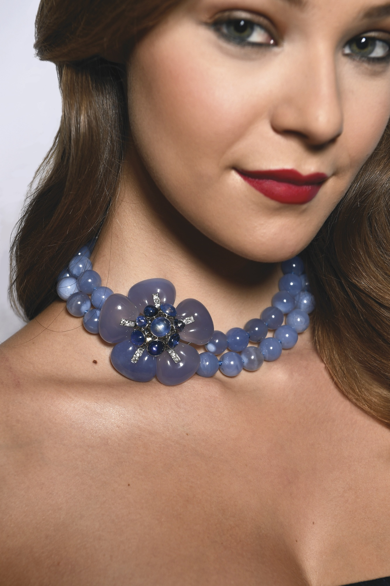 The double-strand necklace composed of 49 chalcedony beads measuring approximately 13.5 mm, gathered at the side with an articulated floral clasp centering eight cabochon sapphires, framed by five carved chalcedony petals, further decorated by trim set with old European-cut diamonds weighing approximately .85 carat, length 15 inches, with French assay and workshop mark for Groëne et Darde; 1932-1937. With fitted box. (Photo by Bryan Bedder/Getty Images for Sotheby's). Estimate: $350-550,000