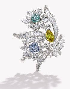The fanciful floral bouquet set with a marquise-shaped Fancy Vivid Yellow, I1 clarity diamond weighing 2.86 carats, a round-cornered square modified brilliant-cut Fancy Intense Blue, VS2 clarity diamond weighing 2.47 carats and a round Fancy Intense Bluish Green, artificially irradiated, SI1 clarity diamond weighing 2.09 carats, accented by marquise-shaped diamonds weighing approximately 7.40 carats, further set with round, baguette and pear-shaped diamonds weighing approximately 9.20 carats, signed Bulgari, with maker's mark; circa 1960