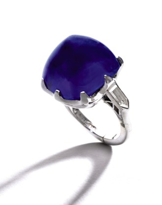 Exceptional Platinum, Sapphire and Diamond Ring. Centering a cushion-cut sugarloaf cabochon sapphire weighing 25.87 carats, and with no indication of heating, flanked by two bullet-cut diamonds weighing approximately .40 carat, size 5; 1930s. This Kashmir sapphire hails from three generations of one of America's most prominent families: that of Thomas Fortune Ryan (1851-1928), who stands alongside J.P. Morgan, Andrew Carnegie and John D. Rockefeller in the annals of American financial history. Est. $3.5/4.5 million