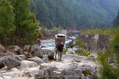 A porter makes his way up the trail along the side of the Dudh Kosi River towards Namche Bazaar.