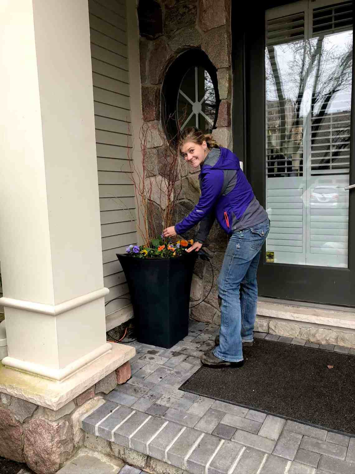 A woman smiles as she helps to create an interesting container arrangement next to the front door of a house. She adds small branches and pansies.