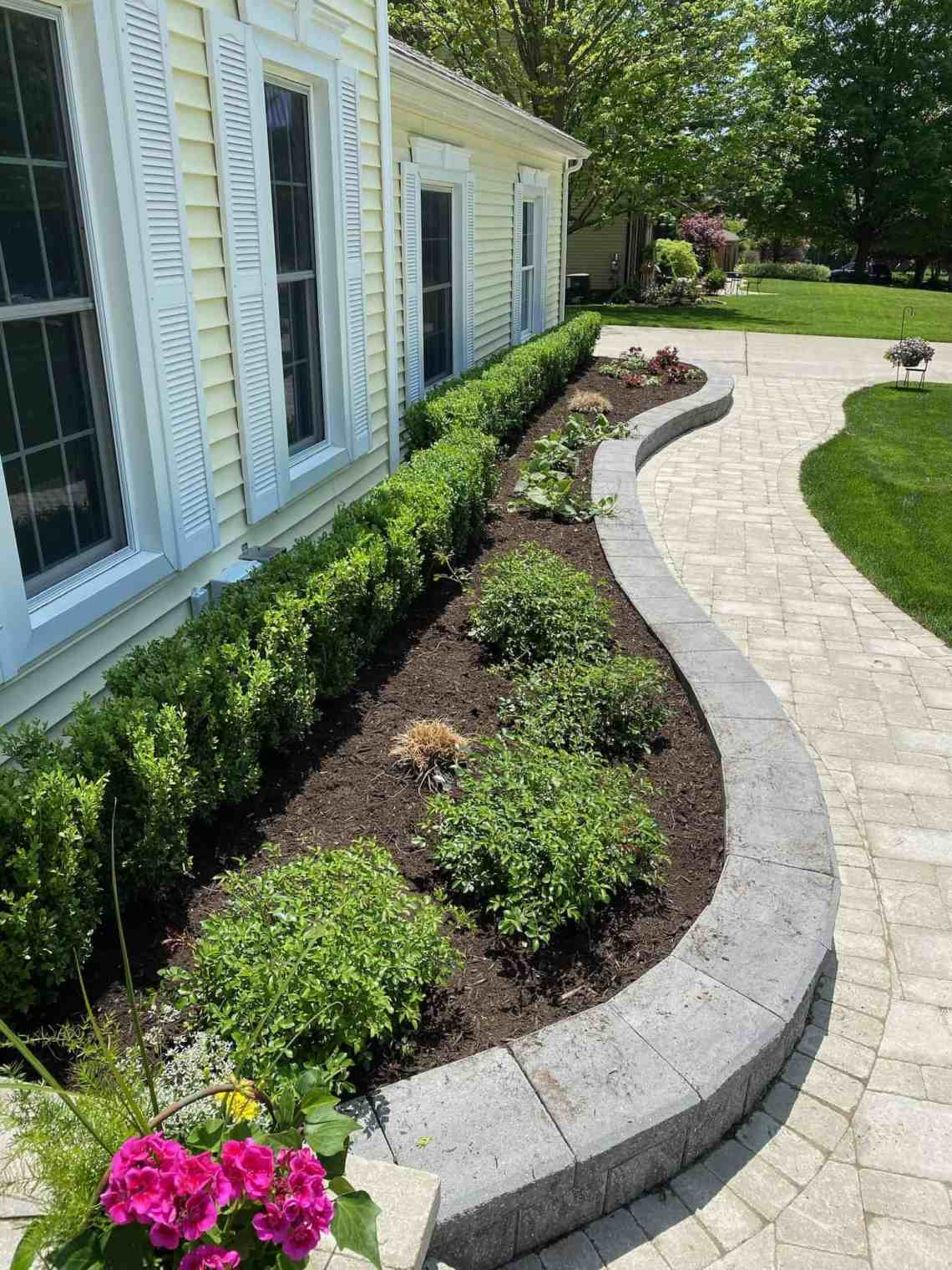 Winding walkways, shrubs, perennials, and a container garden welcome guests at a residence by Highland Horticultural Services