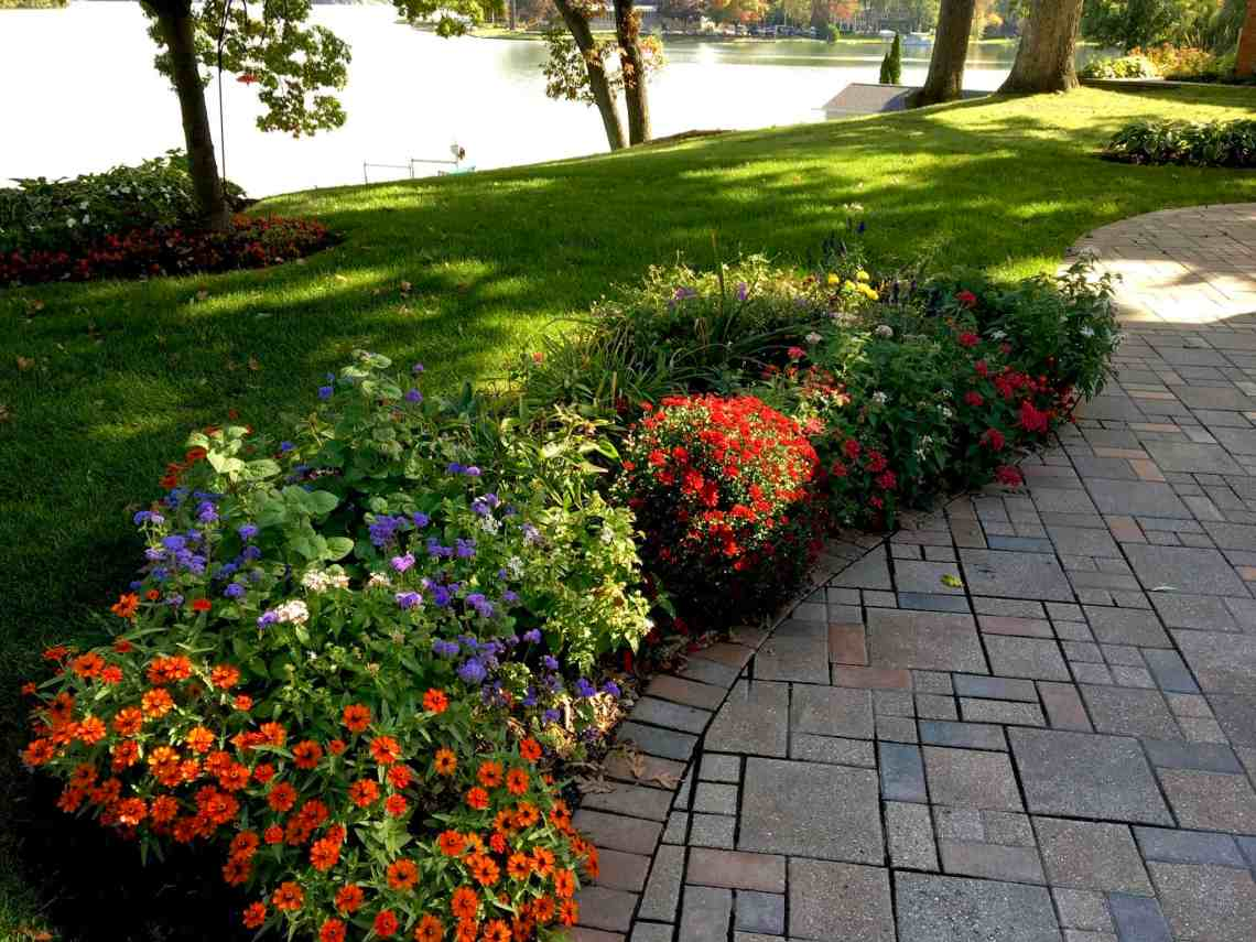 Beautiful gardens by Highland Horticultural include a brick paver patio, colorful flowers, and a neat lawn adjacent to a lake.