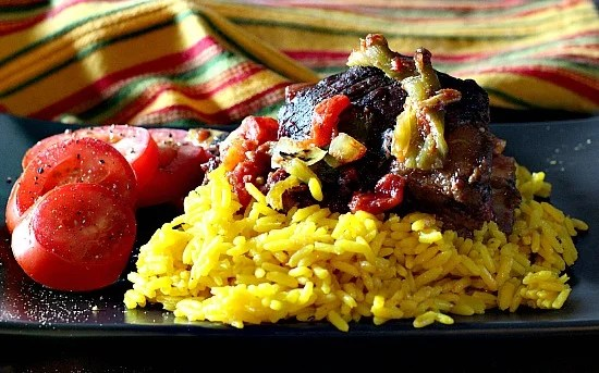 Rick Bayless Braised Mexican Short Ribs with sliced tomatoes on a bed of yellow rice.