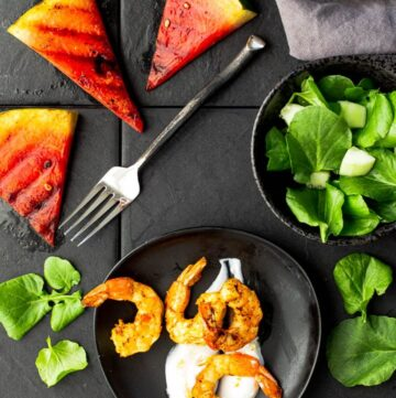 Grilled watermelon wedges with curried shrimp on greek yogurt with a watercress salad