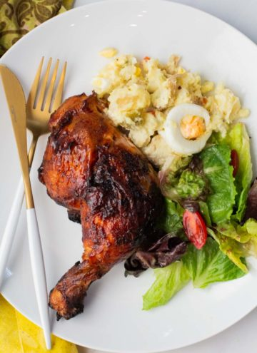 Grilled chicken served with potato salad and a tossed salad.