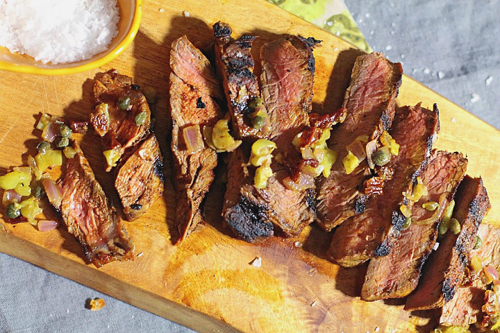 Sirloin steak pan grilled and sliced on a cutting board. Topped with pepperoncini, caper, dijon, sun-dried tomato relish