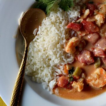 Cream seafood stew with shrimp and white fish. With coconut milk, spices and served with white rice.