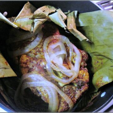 Achiote Paste Shredded Pork Tacos wrapped in banana leaves and topped with onions.