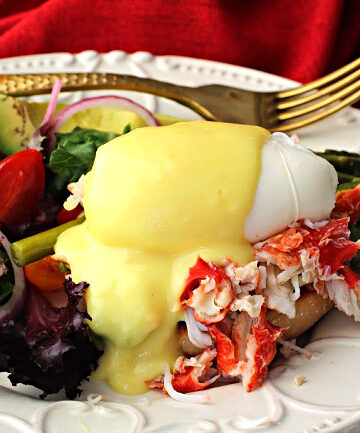 Eggs Benedict with crab meat, asparagus spears topped with Hollandaise Sauce and served with a side salad.