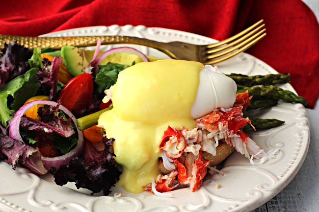 Eggs benedict with crab meat and asparagus spears topped with Hollandaise Sauce and served with a side salad.