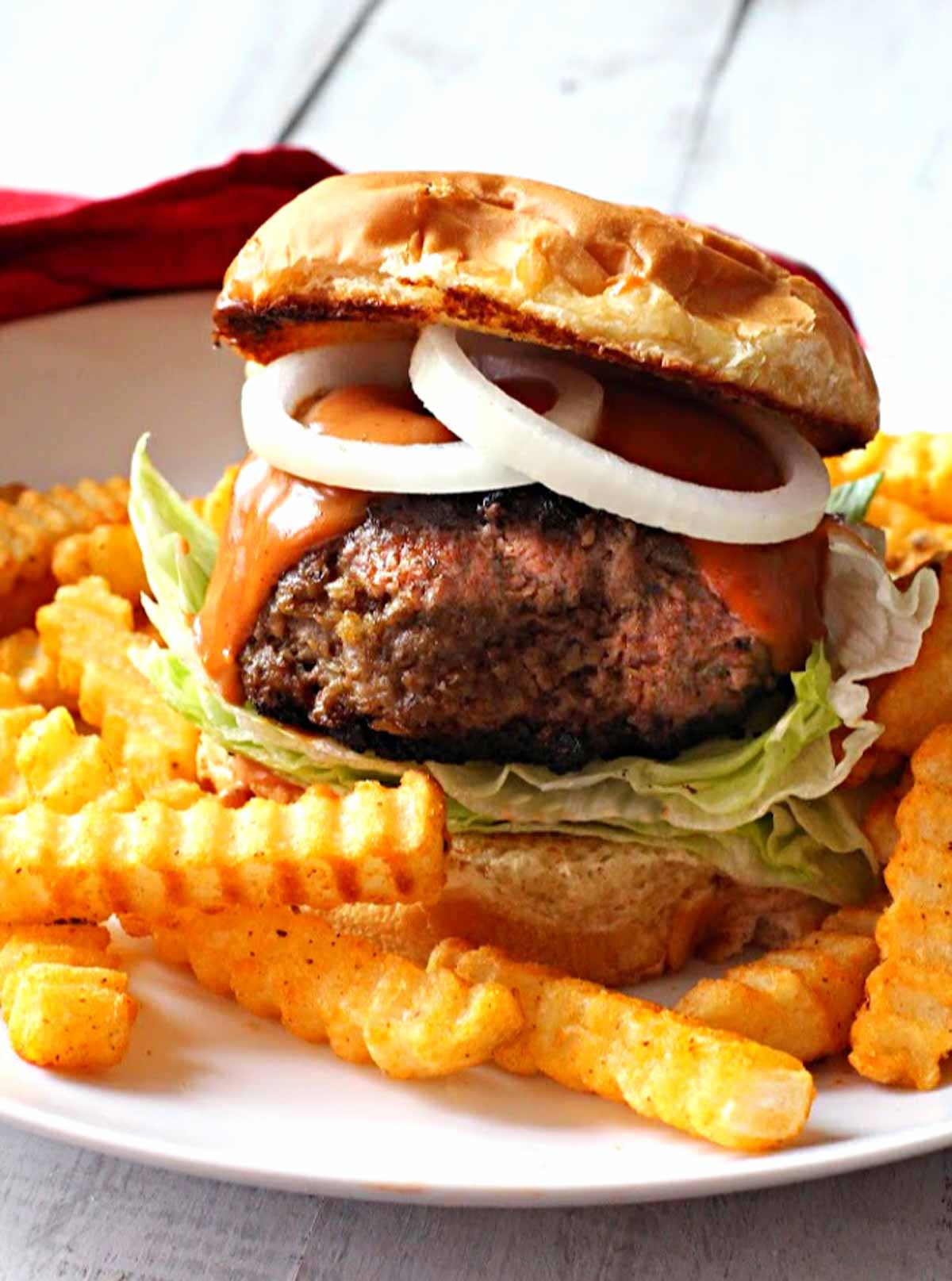 bison burger topped with sauce and onion rings, served with fries