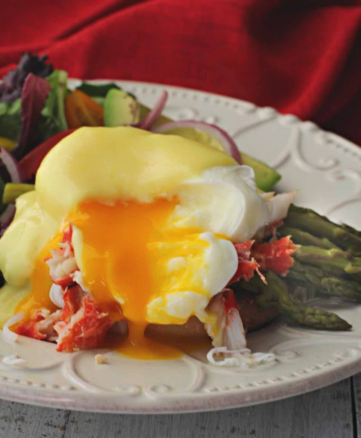 Eggs benedict with crab meat and asparagus served with a side salad