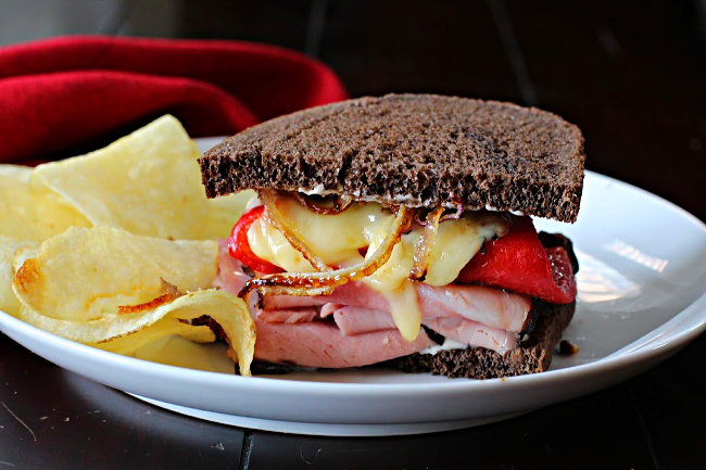 Ham and Manchego cheese sandwich with roasted red bell peppers and caramelized onions on pumpernickel bread