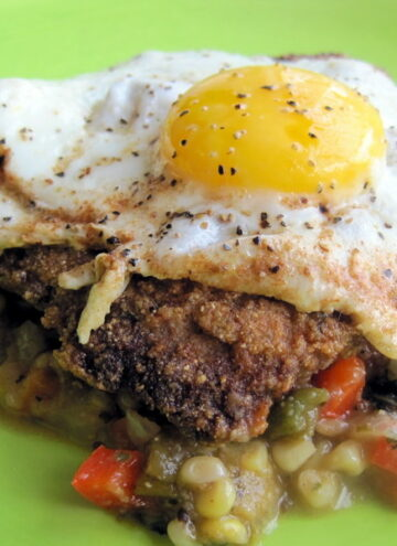 Chicken fried steak over corn relish topped with a fried egg.