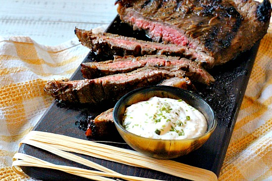 Marinated grilled flank steak on a black wood cutting board with a bowl of horseradish cream sauce