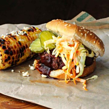 Bobby Flay Texas Burger topped with cole slaw and BBQ sauce served with grilled corn