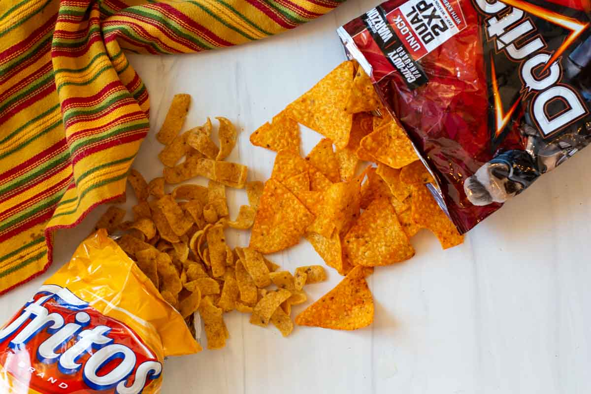 Packages of Doritos and Fritos with chips coming from the top