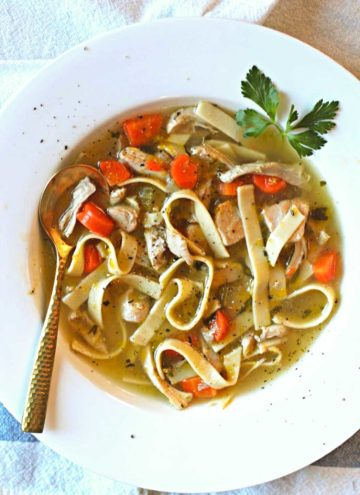 Hearty Chicken Noodle Soup in a white bowl garnished with parsley