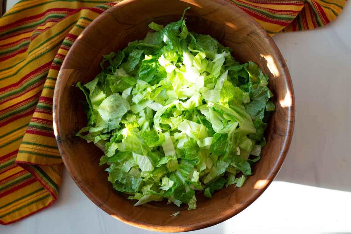 Chopped romaine lettuce and iceberg lettuce in a large wooden salad bowl.