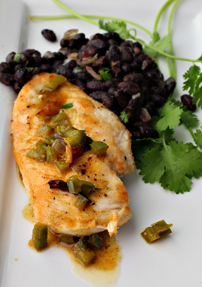 Chicken cutlet recipe topped with orange jalapeno sauce with black beans and cilantro served on a white platter.