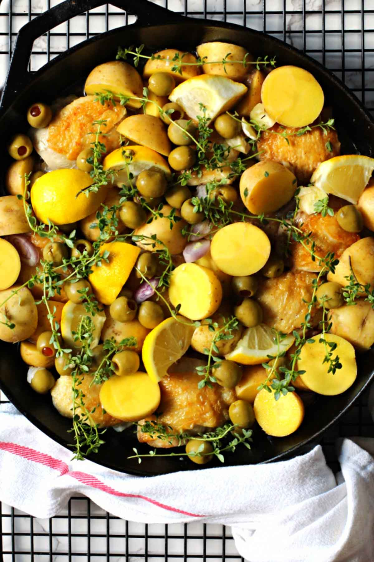 Yukon gold potatoes, chicken thighs, olives cooking in a cast iron skillet