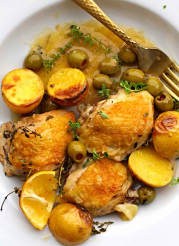 Cast iron skillet braised chicken thighs with potatoes and olives in a broth
